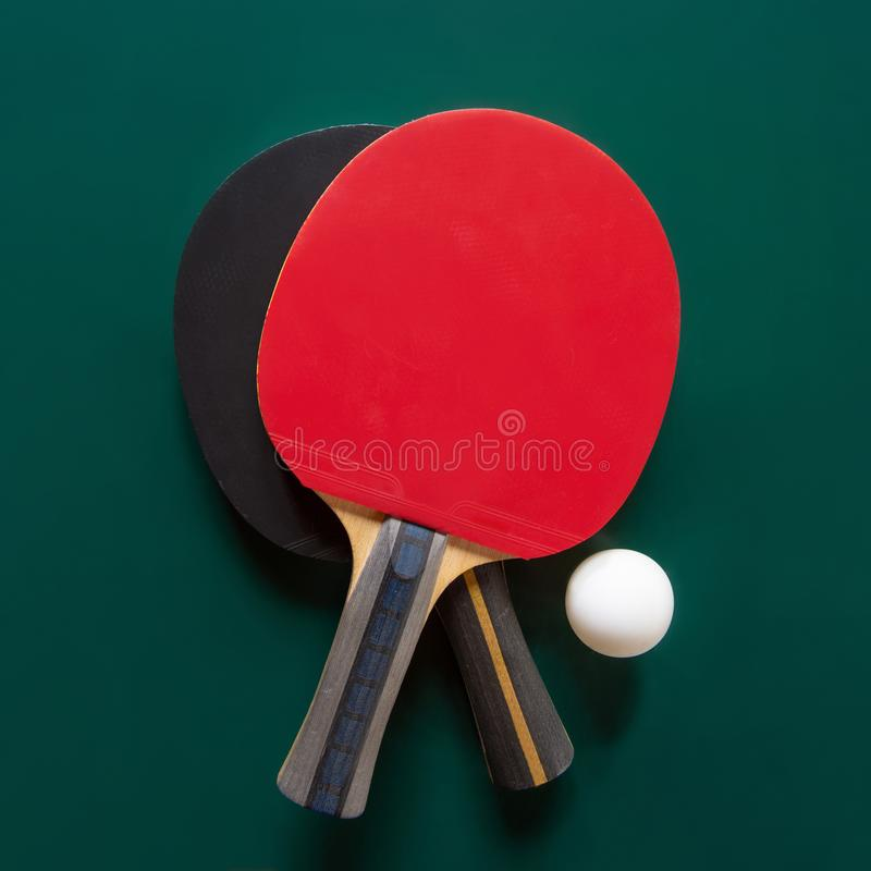 Two ping-pong rackets and a ball on a green table. C stock photo
