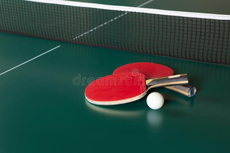 Two ping-pong rackets and a ball on a green table. ping-pong net royalty free stock photos
