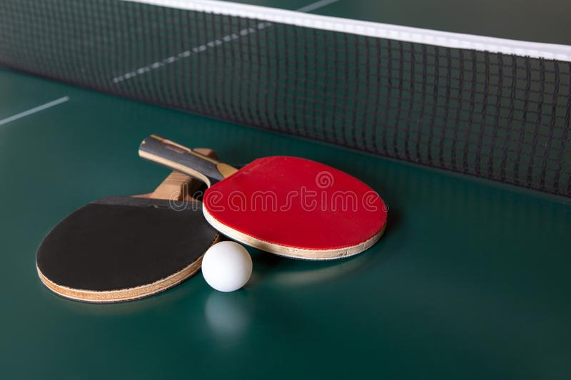 Two ping-pong rackets and a ball on a green table. ping-pong net stock photography