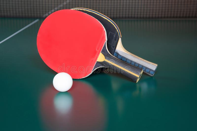 Two ping-pong rackets and a ball on a green table. ping-pong net royalty free stock images