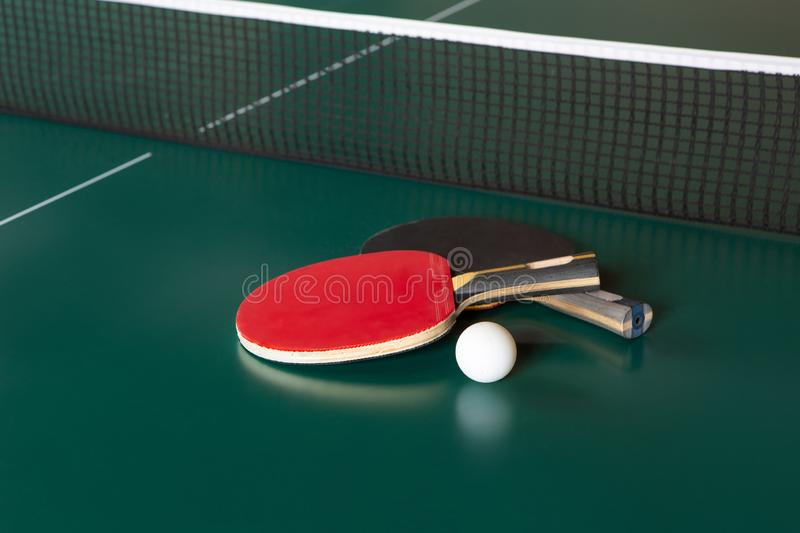 Two ping-pong rackets and a ball on a green table. ping-pong net stock image