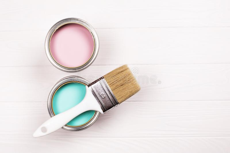 Two pink and blue open paint cans and brush on white wooden background. stock photography