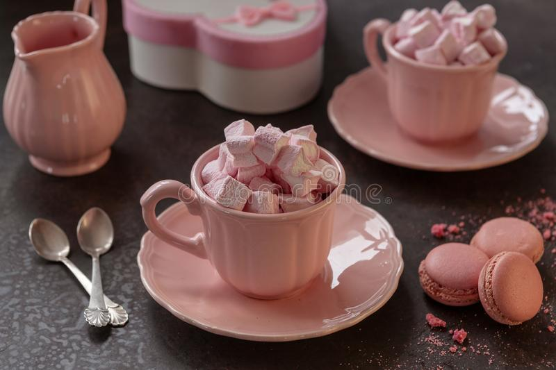 Two pink cups with pink heart-shaped marshmallows, a gift in a pink box and pink macarons. Romantic breakfast for two. Close-up, stock photos