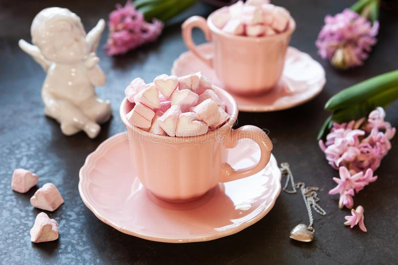 Two pink cups with pink heart shaped marshmallows, pink hyacinths, angel figurine and silver heart shape pendant on chain. stock photo