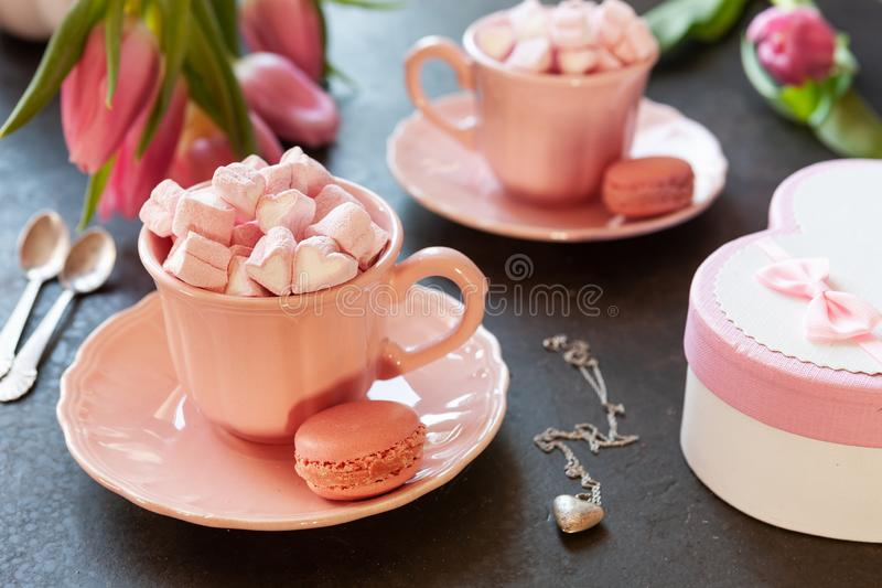 Two pink cups with pink heart shaped marshmallows with macaroons, pink tulips, gift box and silver heart shape pendant on chain. royalty free stock images