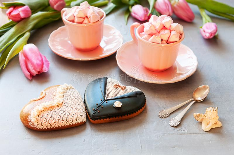 Two pink cups with pink heart shaped marshmallows, pink tulips, angel figurine and two gingerbreads bride and groom form. stock photos