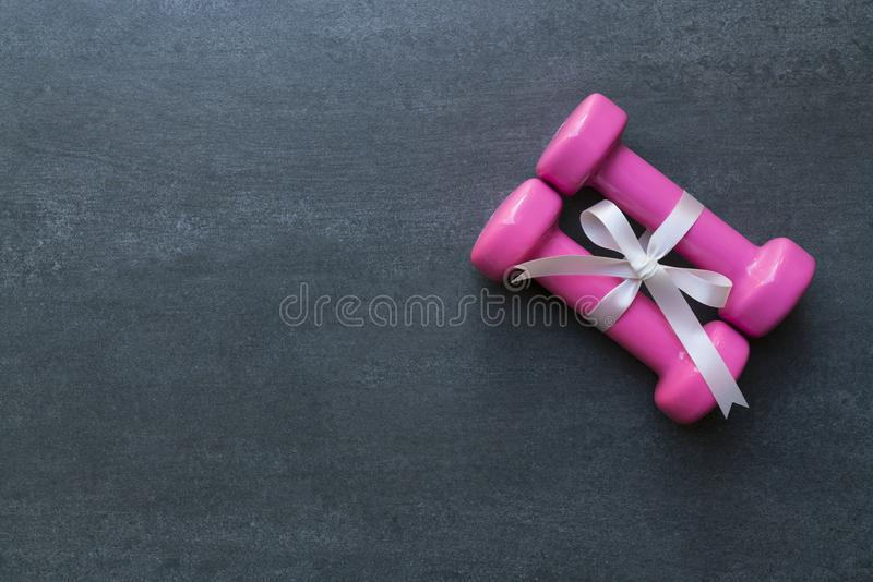 two pink dumbbell with white gift bow on a black table background, sport and healthy concept royalty free stock photography