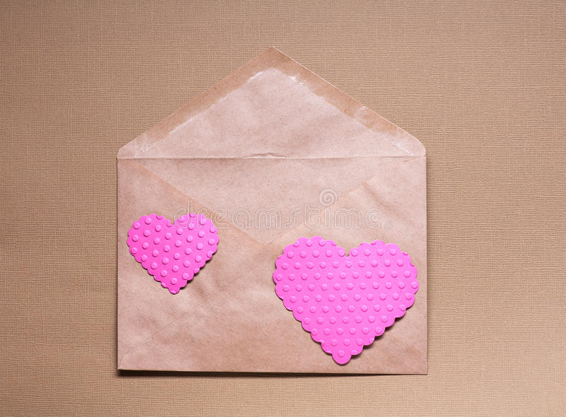 Two pink hearts on craft paper envelop royalty free stock photos