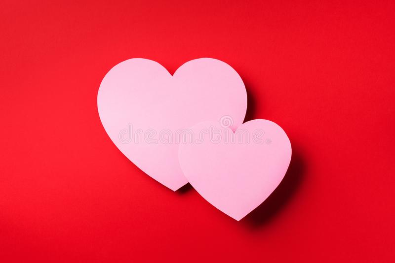 Two pink hearts cutted from paper over red background with copy space. Top view. Valentine`s Day. Love, date, romantic concept stock image
