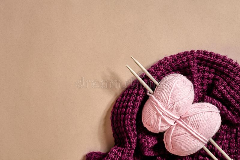 Two pink knitting yarn balls, knitting needles and and purple knitted plaid top view stock photo