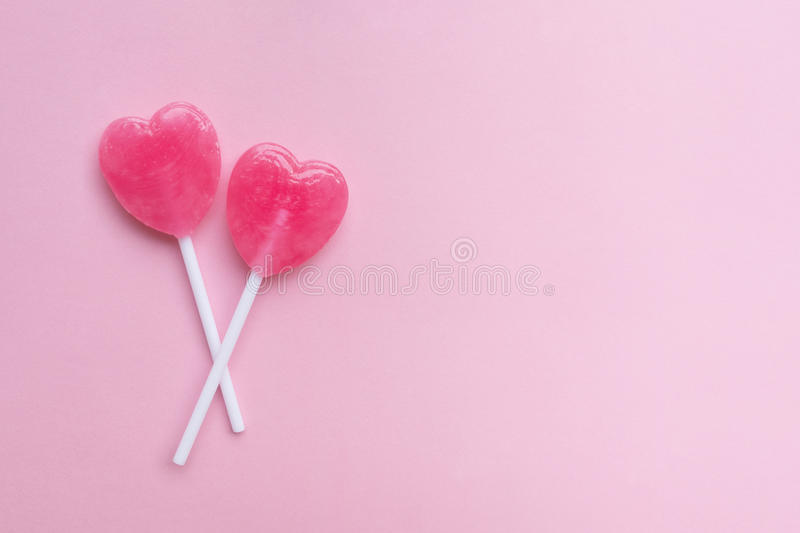 Two Pink Valentine`s day heart shape lollipop candy on empty pastel pink paper background. Love Concept. top view. stock images