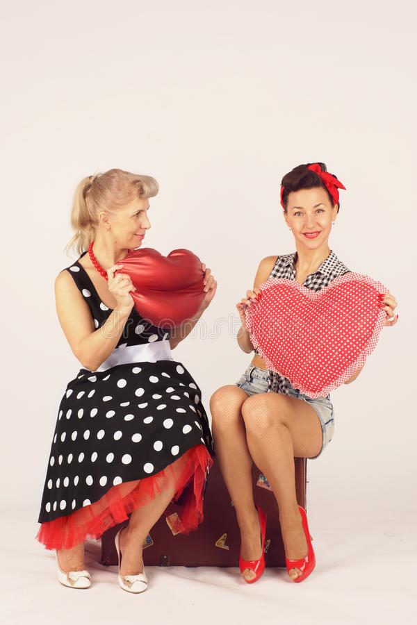 Two pinup girlfriends sit on a road suitcase and hold plush hearts on a white background.  royalty free stock image