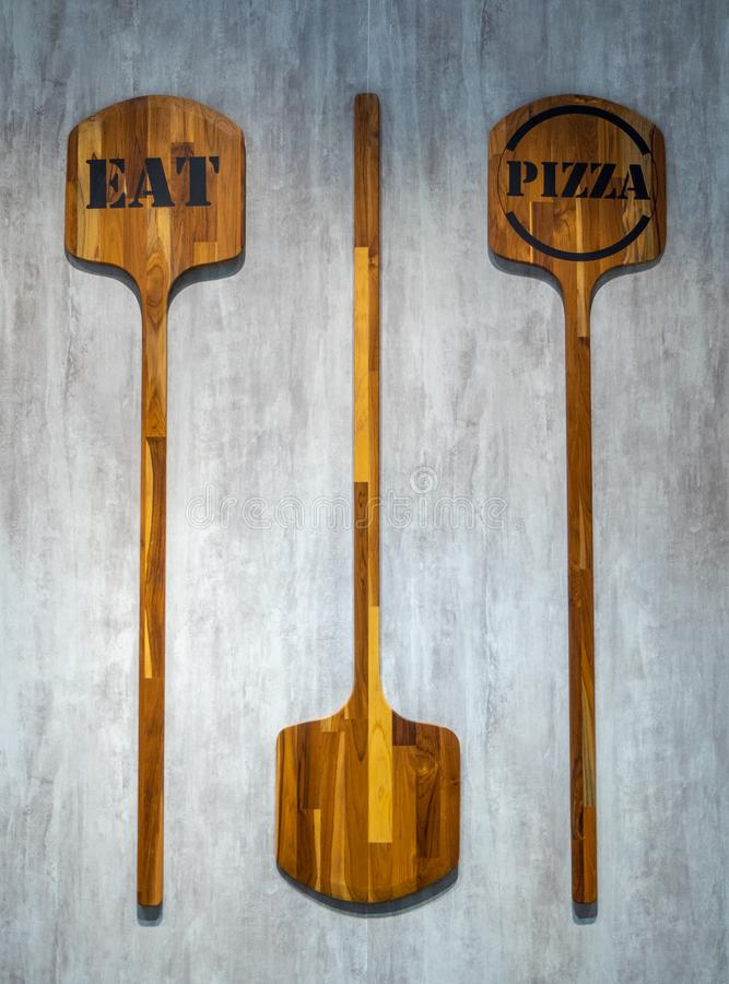 Two pizza paddle with text `eat` and `pizza` hang on wall for background. Two pizza paddle with text `eat` and `pizza` hang on concrete wall for background stock images