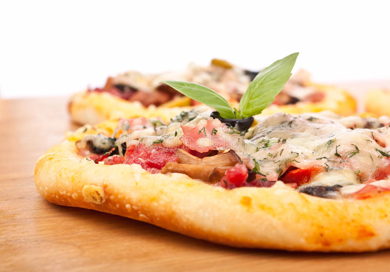 Two Pizzas Close up. Two Mixed Topping Pizzas on Wooden Table Close up stock photography