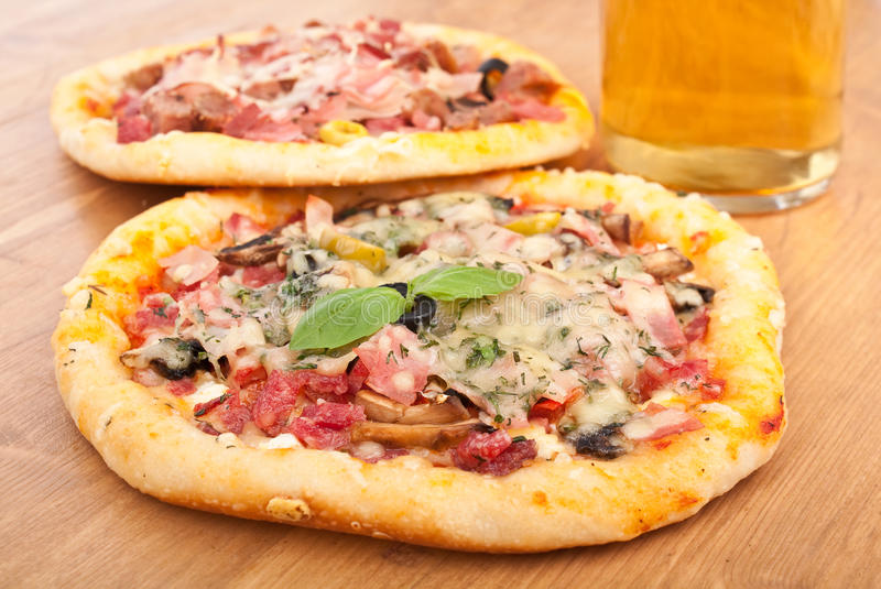 Two Pizzas and a Glass of Beer. Two Mixed Topping Pizzas and a Glass of Beer royalty free stock images