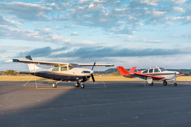 Two Planes On Tarmace At Sunrise. Two small prop plance tied down on the tarmac at sunrise royalty free stock photo