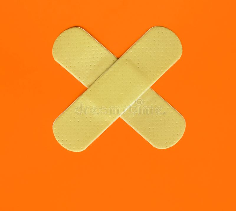 Two plasters forming a cross on orange stock image