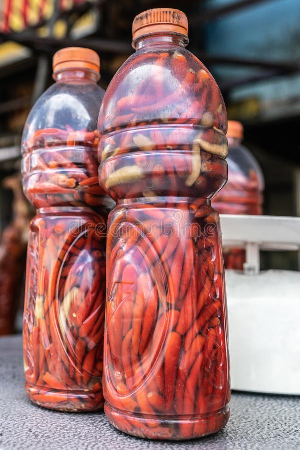 Two plastic bottles filled with red carrots in Manila, Philippines. Manila, Philippines - March 5, 2019: Calavite street in Salvacion part of town. Closeup of royalty free stock photo