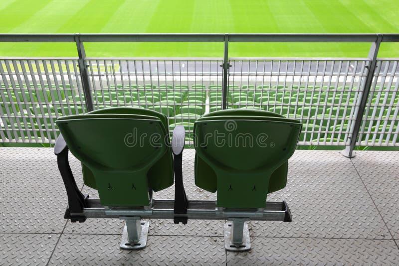 Two plastic seats on tribune of large stadium stock photo