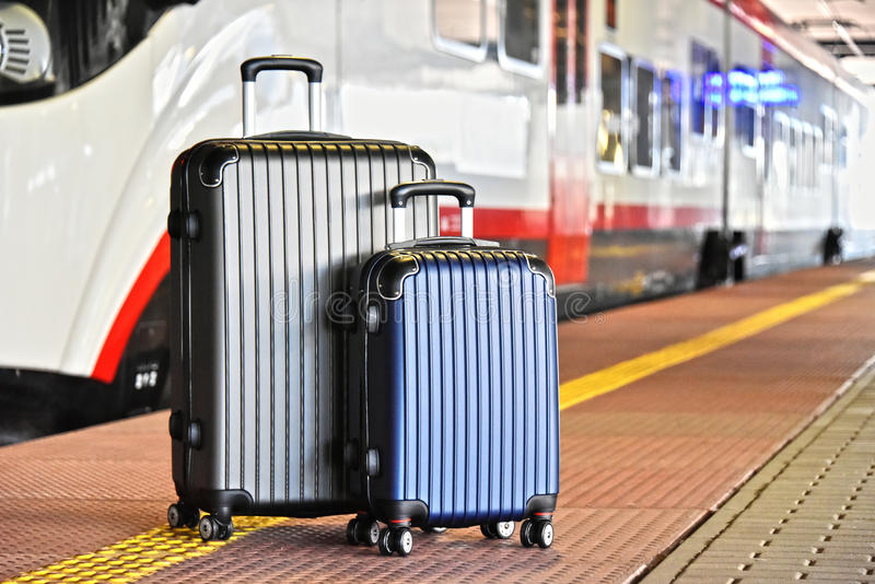 Two plastic travel suitcases on the railroad platform stock images