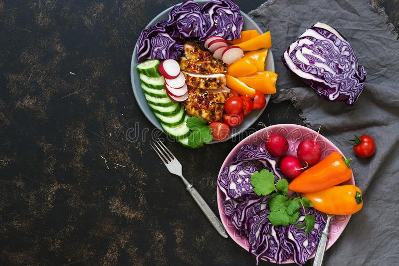 Two plates with fresh vegetables and baked chicken breast on a dark background, top view. Buddha Vovl. Top view, space for your te stock photos