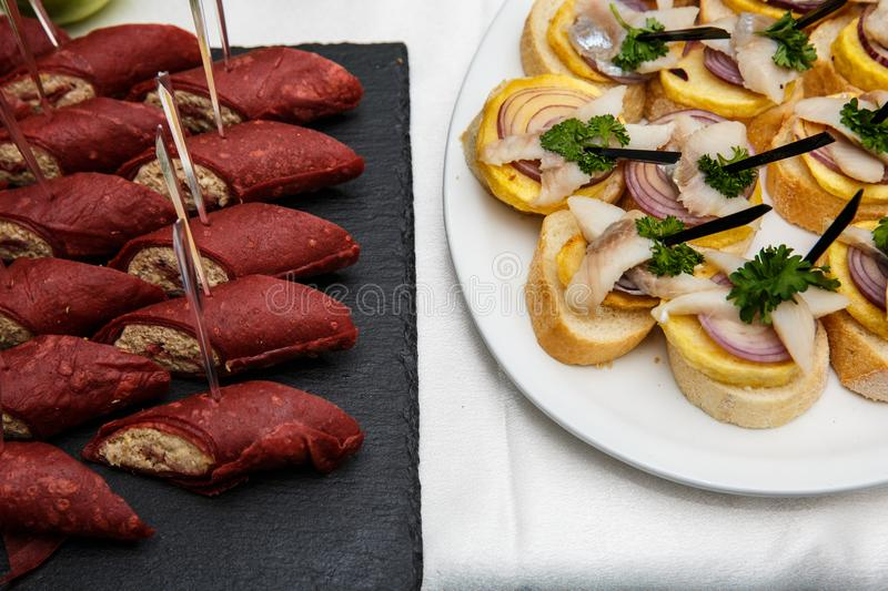 Two plates with snacks on a buffet table. Selection of tasty bruschetta or canapes on toasted baguette with potatoes herring fish, royalty free stock photos