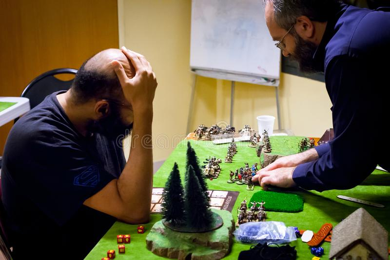 Two adults playing a wargame on board at a wargame convention stock image