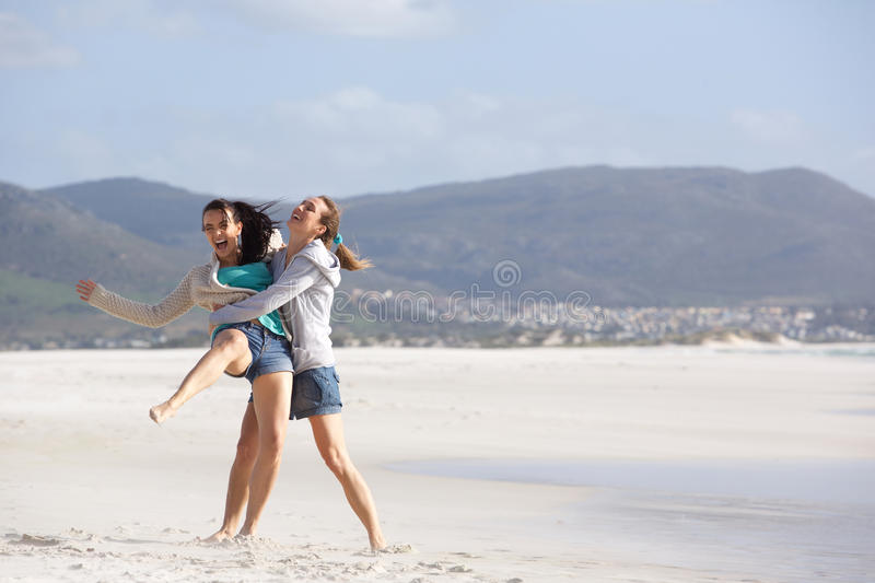 Two playful girlfriends having a good time at the beach stock images