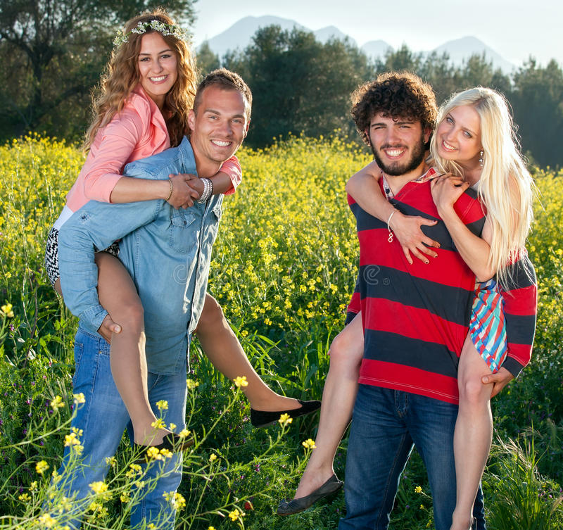 Two playful happy young couples in the country. stock images