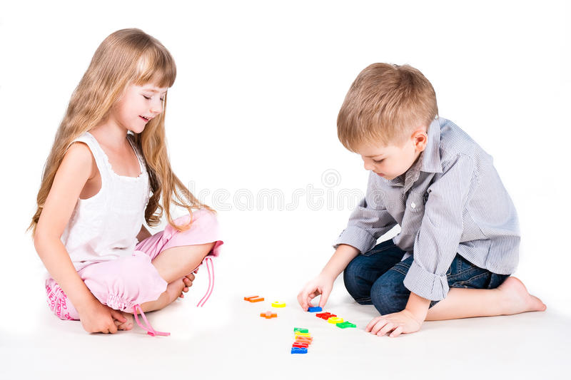 Two playing kids with alphabet isolated on white royalty free stock image