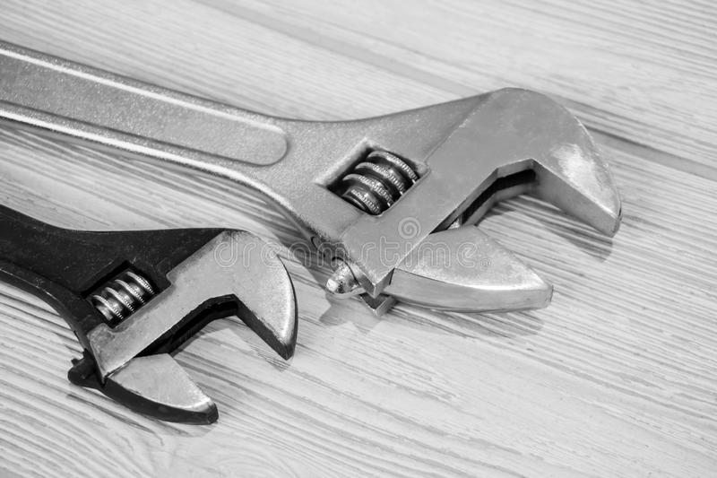 Two adjustable wrenches on the table close up. Two plumbing adjustable wrenches on the light table surface stock images