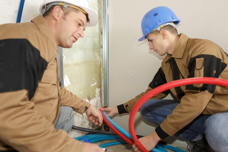 Two plumbing building contractors cut pipe for construction site stock photography