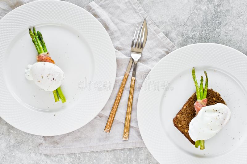 Two poached eggs on roasted asparagus wrapped in bacon. Gray background, top view. stock photo