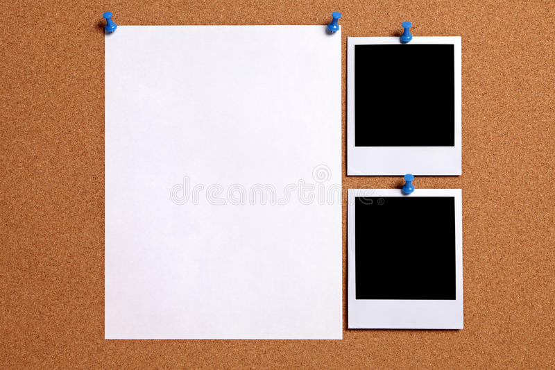 Two polaroid style blank photo frames with paper poster pinned to cork notice board, copy space royalty free stock photos