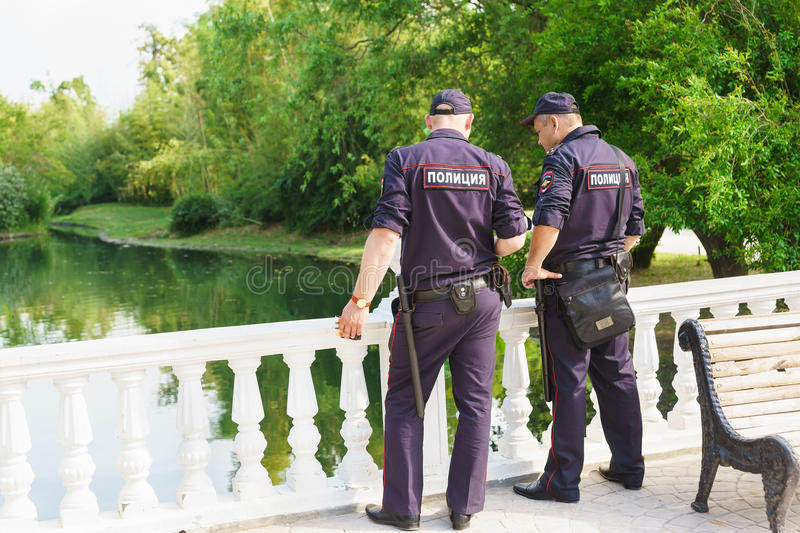 Two police officers follow the rule of law in the dendrological Park royalty free stock image