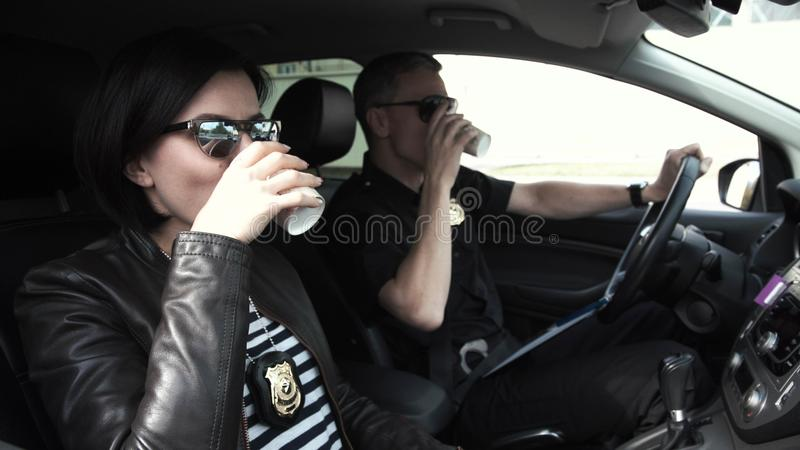 Two police officers sitting in car during break stock photos