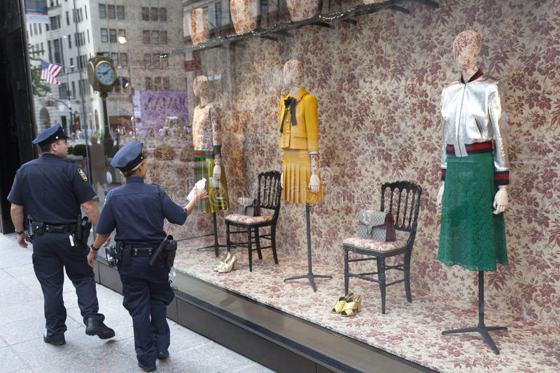 Two police officers walk by tiffany's in new york city stock images