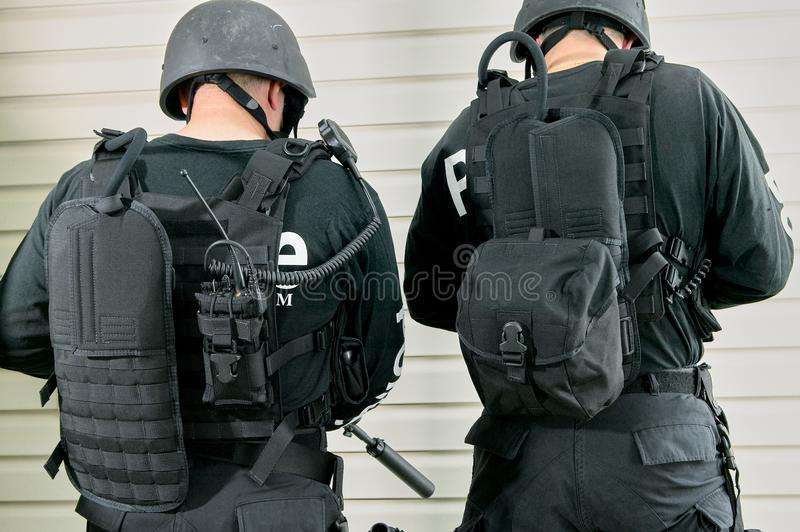 Two police officers wearing different backpacks. Two police officers wearing different styles of backpack to carry their gear standing with their backs to the royalty free stock photos