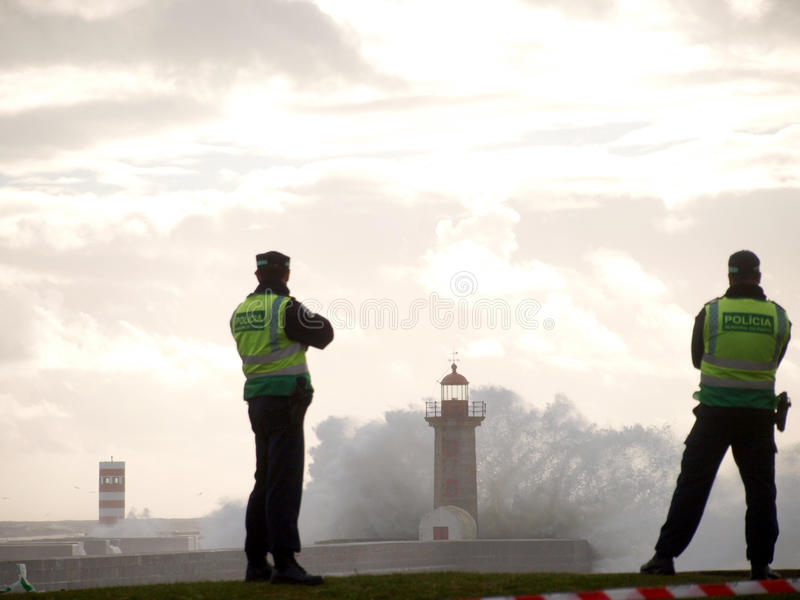 Two policemen watch big wave cover the lighthouse this sunday in oporto. stock photography