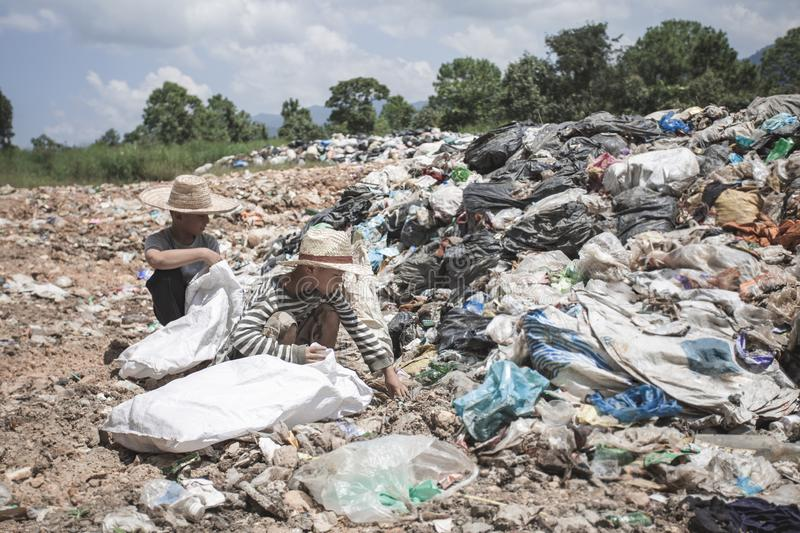 Two poor children help to collect and sort waste for sale, the concept of poverty and the environment stock photography