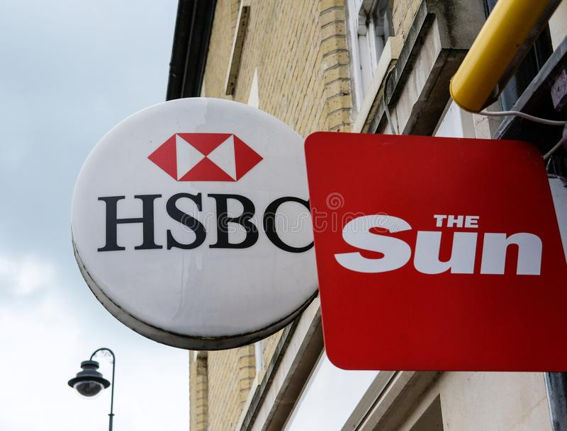 Well-known bank and newspaper signs seen outside a newsagent. Two popular logo`s, once for a retail bank and the other for a tabloid newspaper in the UK stock image