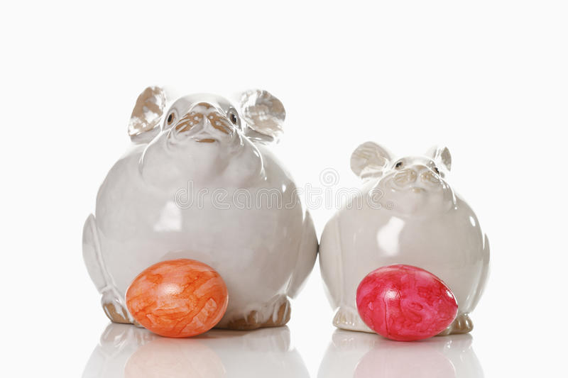 Two porcelain Easter bunny on white background with dyed Easter eggs royalty free stock images