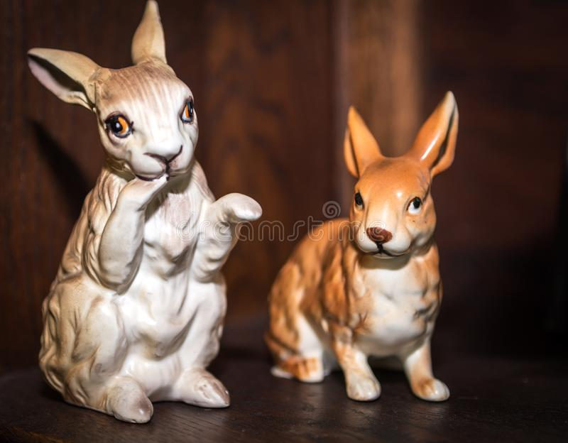 Two porcelain vintage bunny figurines with wooden background. Easter Concept stock photos