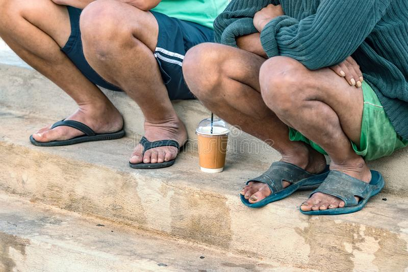 Two port workers taking a break sitting with sandals on their feet and having cold coffee in Heraklion, Greece. Two port workers taking a break sitting with royalty free stock image