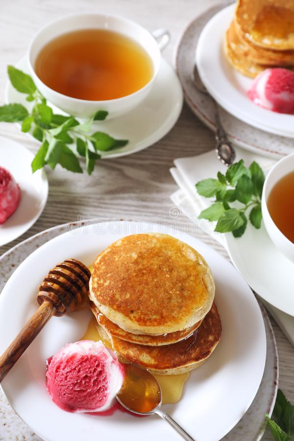 Banana pancakes with honey and fruit sorbet and cups of green tea stock images