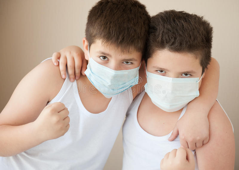 Two positive boys in medical masks royalty free stock photos