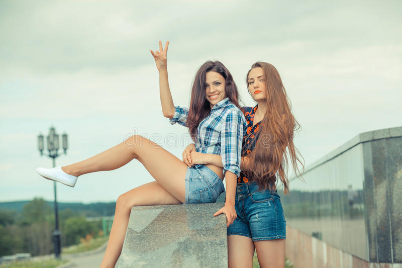 Two positive hipster girlfriends. Friends girls communicate outdoors in the city royalty free stock photography