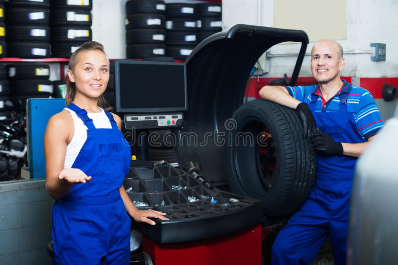 Two positive technicians working in car service. Two positive technicians working on wheel balancing machinery in car service royalty free stock image