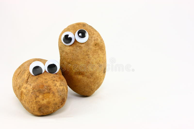 Two Potato Friends With Wiggly Eyes. Two brown russet potatoes decorated with plastic wiggly eyes to create fun food characters stock images