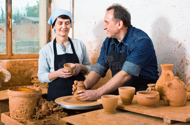 Two potters in the process of work at the workshop. Two cheerful positive potters in the process of work at the workshop stock photography